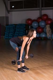 Mulher realizando exercício de levantamento terra com barra de peso
