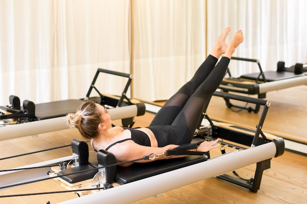 Mulher realizando os cem exercícios de pilates
