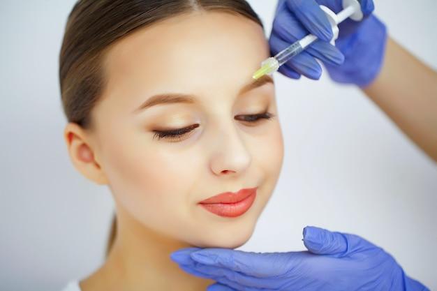 Mulher recebe injeção na cara dela.
