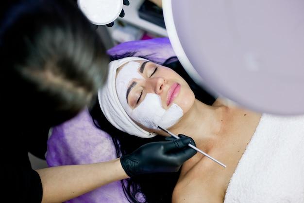 Mulher recebe máscara de casca de rosto, tratamentos de spa, cuidados com a pele em salão de beleza