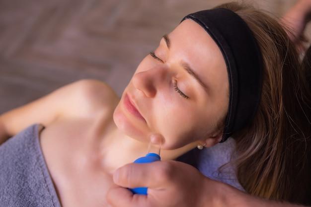 Mulher recebe massagem facial de rejuvenescimento facial no spa de bem-estar de acupuntura.