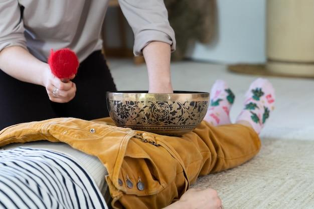 Mulher recebe massagem tibetana com tigela de canto e terapia de som da prática médica tradicional do nepal