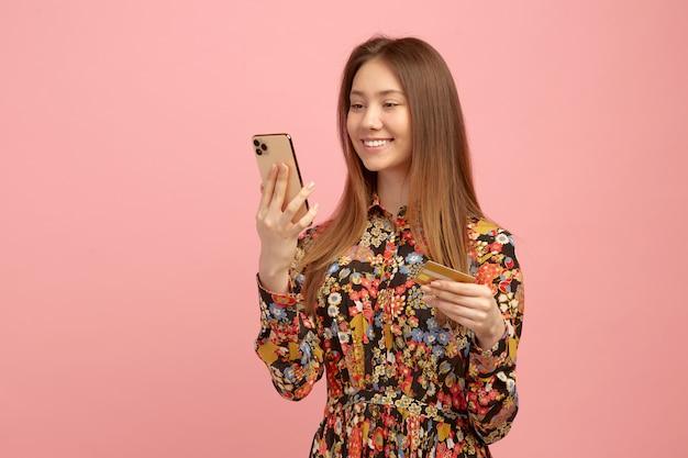 Mulher recebe serviços bancários, uma compra on-line, usando um cartão de crédito com uma oferta de estudante, tem um telefone celular nas mãos.