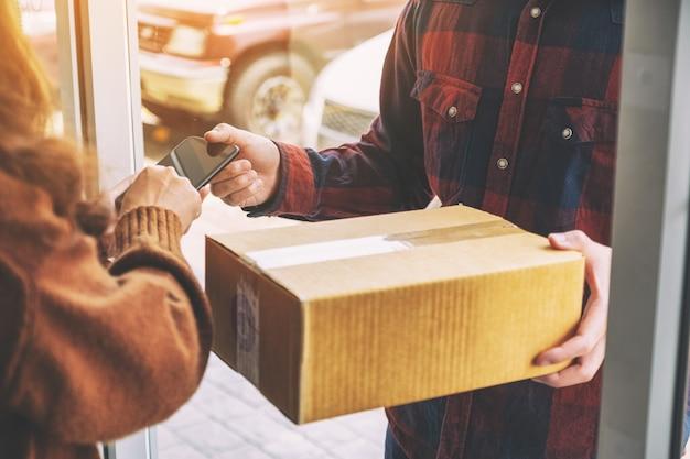 Mulher recebendo a caixa do pacote e assinando o nome ao telefone com o entregador na porta de casa