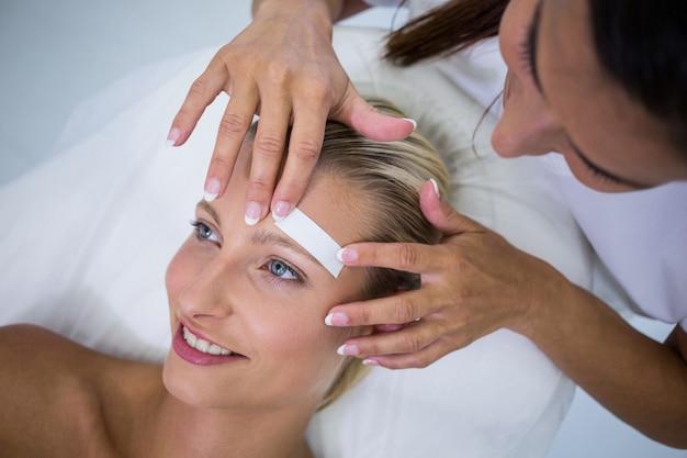 Mulher recebendo as sobrancelhas em forma