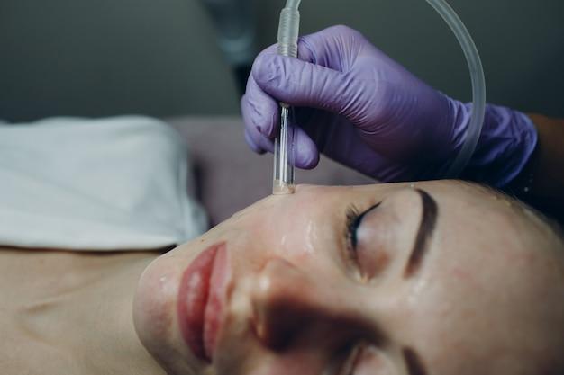 Mulher recebendo aspirador de pó para tratamento facial em clínica de beleza ou spa