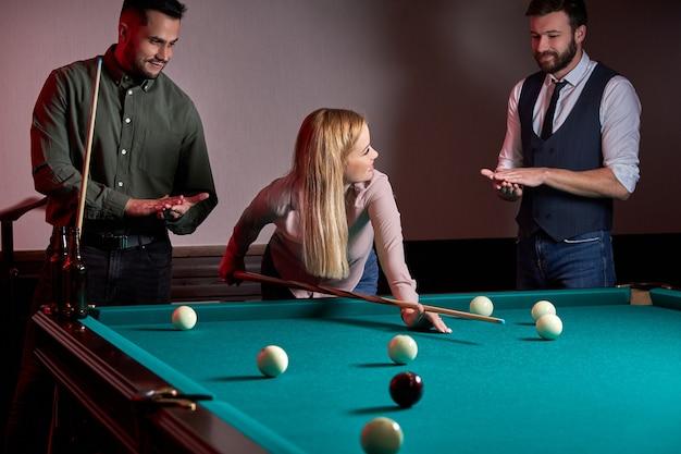 Mulher recebendo conselhos sobre como jogar bilhar enquanto joga bilhar com amigos, concentrada em jogos esportivos