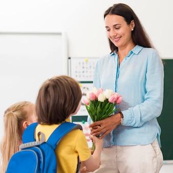 Mulher recebendo flores de seus alunos