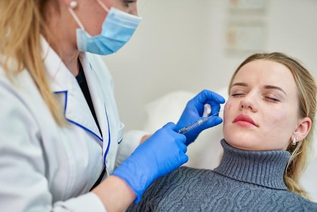 Mulher recebendo injeção cosmética de botox perto dos olhos, close-up
