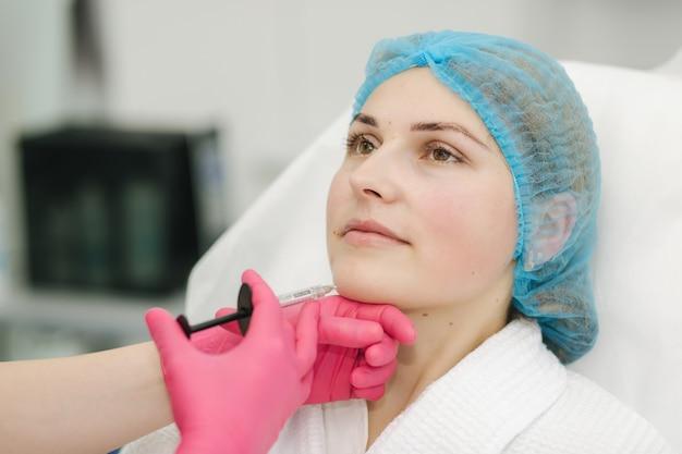 Mulher recebendo injeção de beleza no rosto em salão de beleza