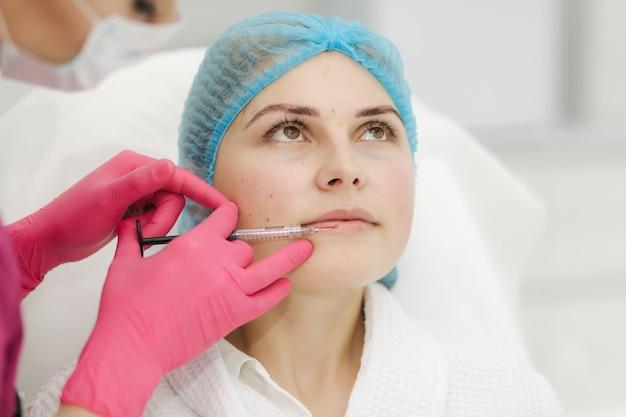 Mulher recebendo injeção de beleza para os lábios em salão de beleza