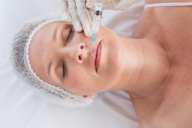 Mulher recebendo injeção de botox em seus lábios
