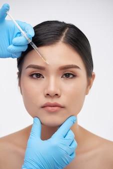 Mulher recebendo injeção de preenchimento