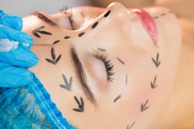 Mulher recebendo injeção na testa