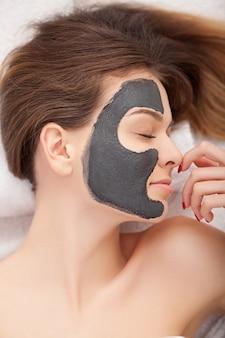 Mulher recebendo máscara facial no salão de beleza