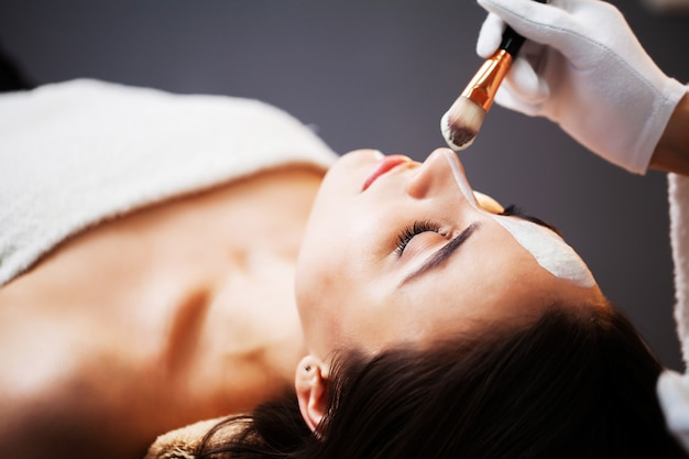 Mulher recebendo máscara facial spa no centro de beleza