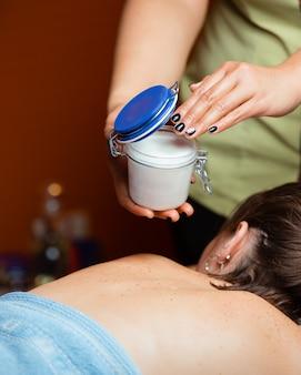 Mulher recebendo massagem com óleo em frasco hermético