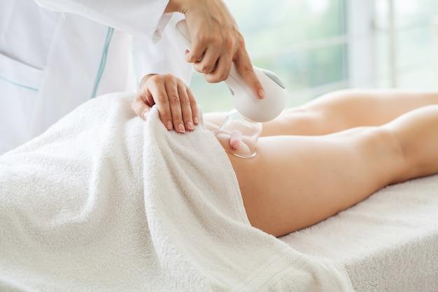Mulher recebendo massagem de glp para cuidados com a pele no estúdio de beleza.