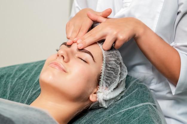 Mulher recebendo massagem de rosto.