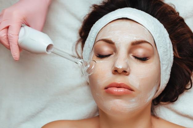 Mulher recebendo massagem facial a vácuo em clínica de estética