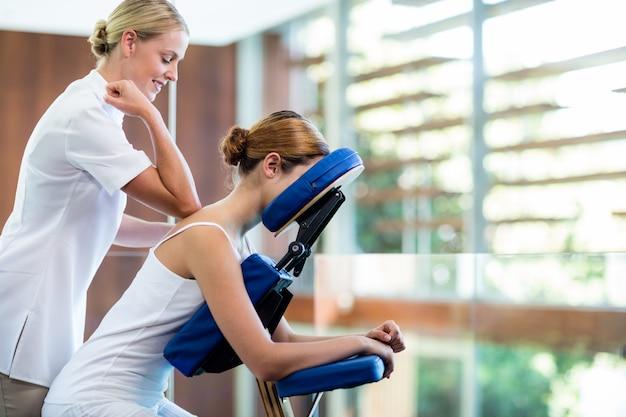 Mulher recebendo massagem na cadeira de massagem