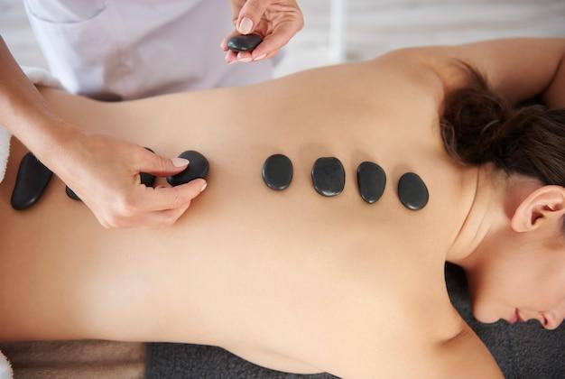 Mulher recebendo massagem nas costas com pedras quentes