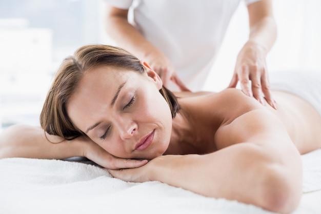Mulher recebendo massagem nas costas do massagista