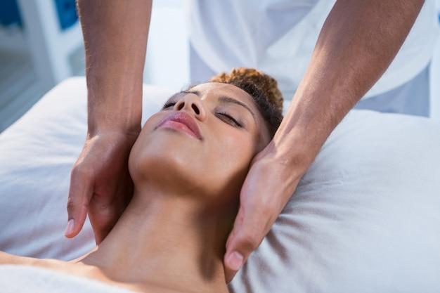 Mulher recebendo massagem no pescoço do fisioterapeuta