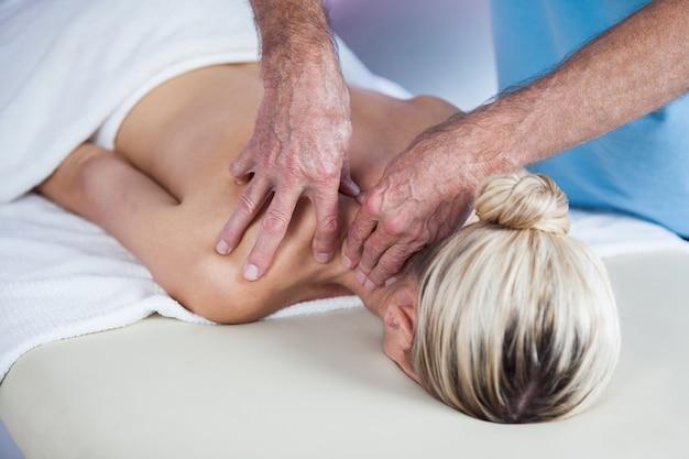 Mulher recebendo massagem nos ombros do fisioterapeuta