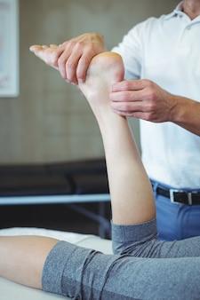Mulher recebendo massagem nos pés do fisioterapeuta