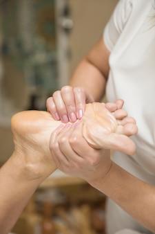 Mulher recebendo massagem nos pés no salão spa