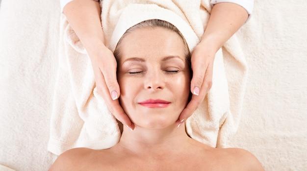 Mulher recebendo massagem para rosto e pescoço em salão de spa