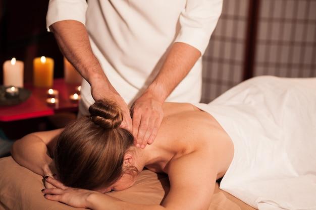 Mulher recebendo massagem relaxante no pescoço, no centro de bem-estar. massagista profissional masculino, massageando o pescoço da cliente do sexo feminino. mulher, desfrutando de tratamento de spa no hotel de luxo. recreação, relaxamento