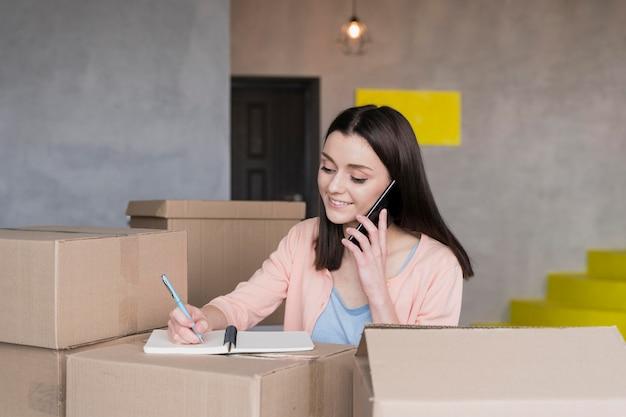 Mulher recebendo ordens de casa cercada por caixas