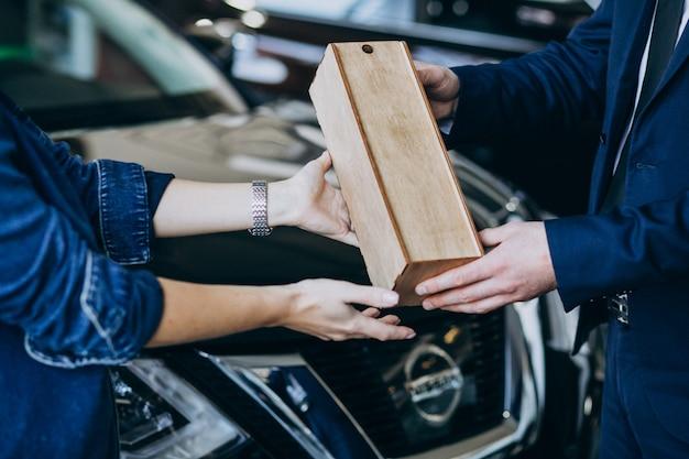 Mulher recebendo parcela de madeira em uma sala de exposições de carros