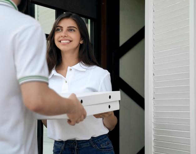 Mulher recebendo pizza do correio