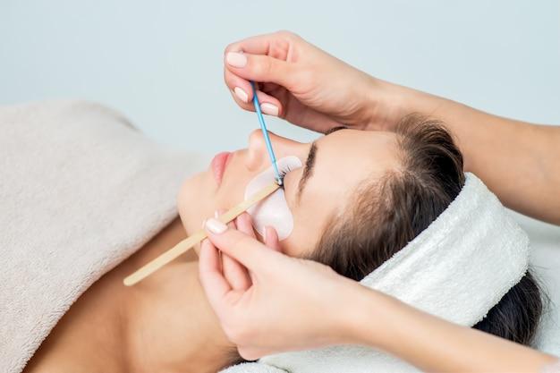 Mulher recebendo procedimento de extensão da pestana.