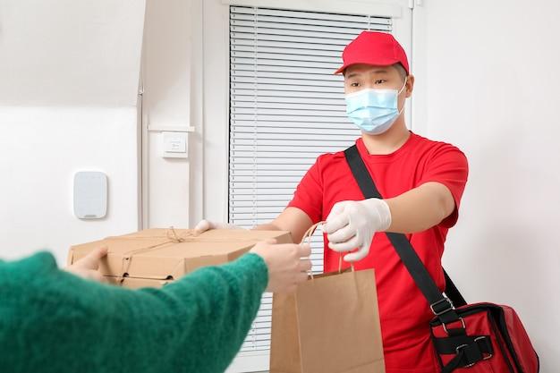 Mulher recebendo seu pedido do correio de serviço de entrega de comida