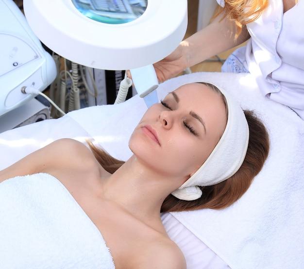 Mulher recebendo terapia de limpeza com um equipamento ultrassônico profissional no consultório de cosmetologia