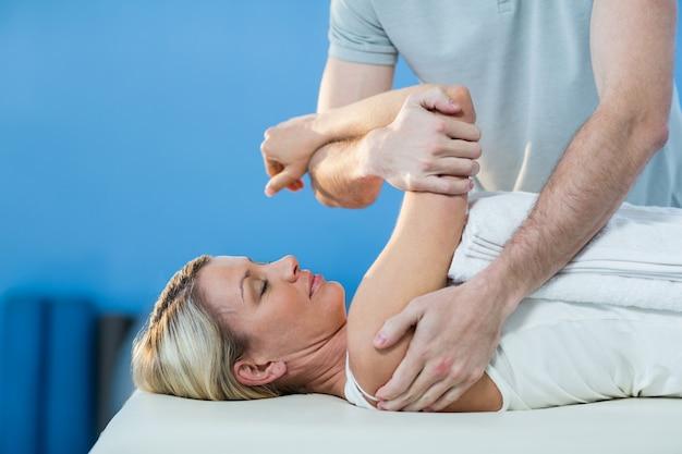 Mulher recebendo terapia do ombro do fisioterapeuta