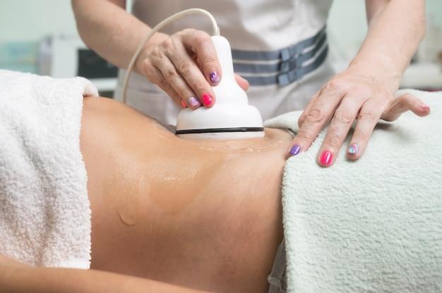 Mulher recebendo tratamento de cavitação por ultrassom por cliente cosmetologista tomando anticelulite ...