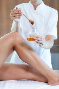 Mulher recebendo tratamento de spa com mel