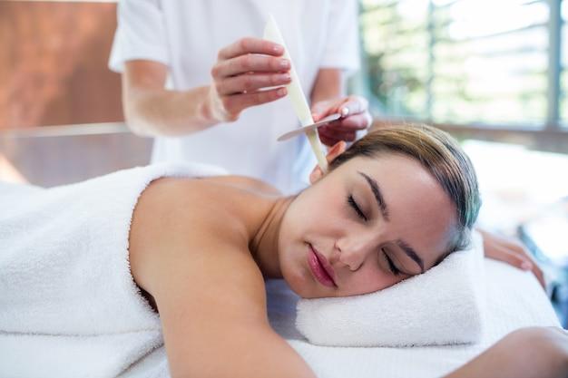 Mulher recebendo tratamento de vela de orelha