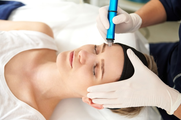 Mulher recebendo tratamento facial de peeling de hidro microdermoabrasão no centro de spa. hydra aspirador de pó. esfoliação, rejuvenescimento e hidratação. conceito de cuidados com a pele