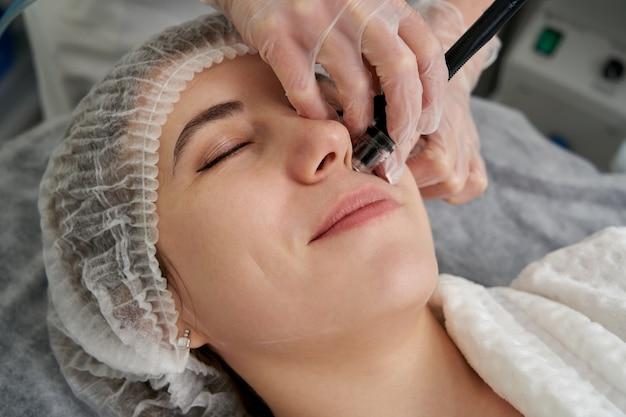 Mulher recebendo tratamento facial hydro microdermoabrasão peeling na clínica de spa de beleza cosmética. hidra