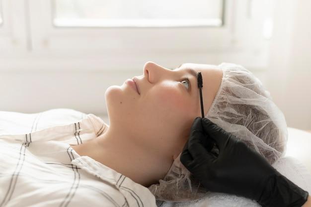 Mulher recebendo tratamento para sobrancelha no salão de beleza