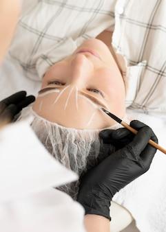 Mulher recebendo tratamento para sobrancelha