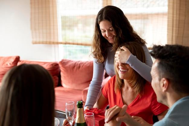 Mulher recebendo um presente no jantar cercada pela família
