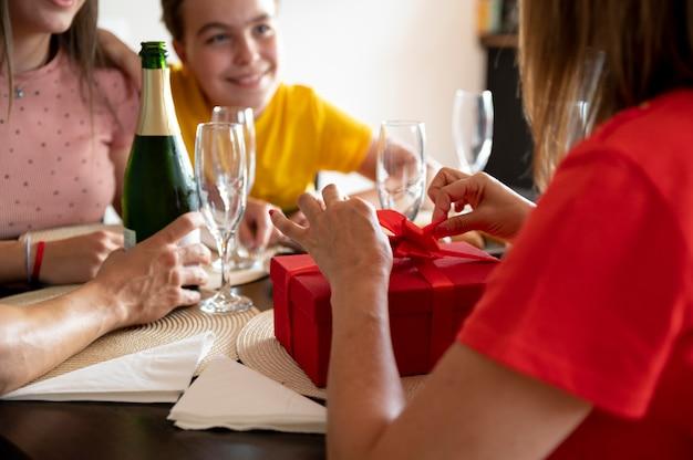 Mulher recebendo um presente no jantar cercada pela família Foto gratuita