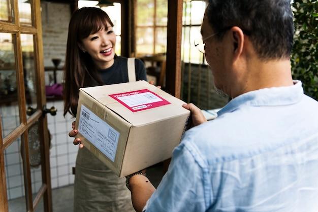 Mulher recebendo uma caixa entregue a ela